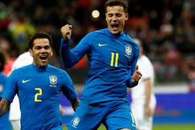 Brazil's Philippe Coutinho (right) celebrating with Dani Alves after scoring.