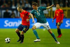 Spain midfielder Andres Iniesta (left) holding Germany's Thomas Mueller at bay.