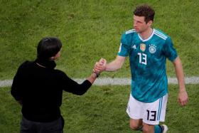 Thomas Mueller (right) shaking hands with Germany coach Joachim Loew after coming off in the 1-1 draw with Spain last week.