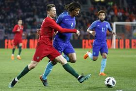 Holland defender Nathan Ake (in blue) challenging Portugal's Cristiano Ronaldo for the ball.
