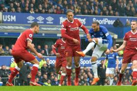 Everton's Cenk Tosun (in blue) shooting at goal.