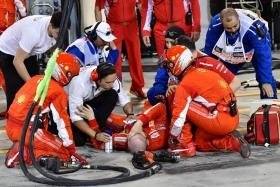 Ferrari's mechanic is attended by his fellow crew after an accident during the Bahrain Formula One Grand Prix at the Sakhir circuit in Manama.