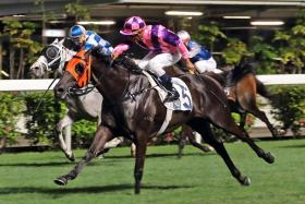 Jockey Karis Teetan taking a look to his right when winning on Pretty Bauhinia in the night's trophy race at Happy Valley on Wednesday.