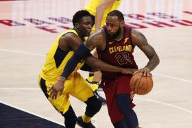 LeBron James driving to the basket against Indiana Pacers guard Victor Oladipo.