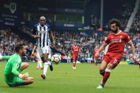 Liverpool's Mohamed Salah (right) lifting the ball over West Brom goalkeeper Ben Foster for the Reds' second goal.