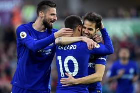 Cesc Fabregas celebrating with Olivier Giroud and Eden Hazard after scoring.