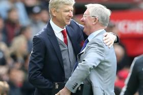 Former Manchester United manager Sir Alex Ferguson (right) presenting Arsenal manager Arsene Wenger with a memento before a match at Old Trafford on April 29.