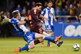 Barcelona's Lionel Messi is challenged by Deportivo La Coruna's Portuguese defender Luisinho.