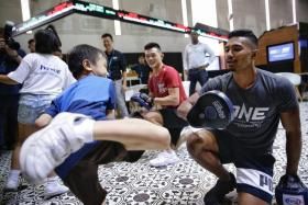 Amir Khan (right) and Christian Lee (in red) at a workshop with underprivileged youths at SGX Centre yesterday.