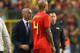 Belgium coach Roberto Martinez having a word with Vincent Kompany, who had to be taken off due to a groin injury.