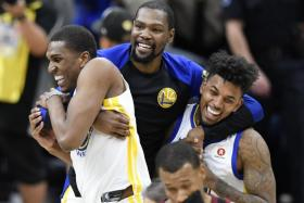 Golden State Warriors forward Kevin Durant (middle) celebrating with forward Kevon Looney (left) and guard Nick Young (right).