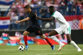 Croatia's Andrej Kramaric surging ahead with Senegal's Salif Sane in close pursuit.