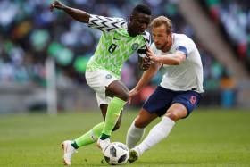 Nigeria's Oghenekaro Peter Etebo (left) in action with Harry Kane during an international friendly on June 12.