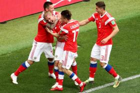Russia's Yury Gazinsky (second from left) celebrates with teammates after scoring the opening goal of the 2018 World Cup in their game against Saudi Arabia.