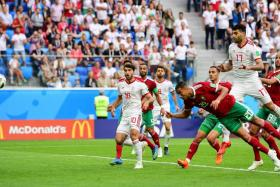 Morocco's Aziz Bouhaddouz heading the ball into his own net while trying to clear an Iran cross in stoppage time.