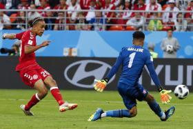 Denmark's forward Yussuf Poulsen (left) scoring a goal past Peru's goalkeeper Pedro Gallese.
