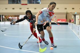 Singapore women's floorball captain Amanda Yeap (right) fending off the challenge of Indonesia's Rahmadani Eka Anjar in the group stage.
