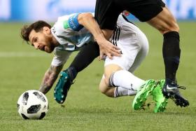 Lionel Messi goes down under the challenge of Croatia's Ivan Strinic.
