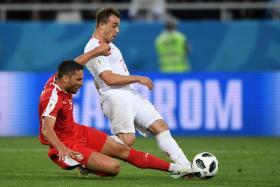 Switzerland forward Xherdan Shaqiri (in white) scoring their winner as Serbia defender Dusko Tosic closes in.
