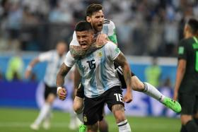 Marcos Rojo carrying Lionel Messi as they celebrate the former's winner.