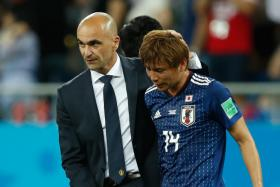Belgium's coach Roberto Martinez comforting Japan midfielder Takashi Inui after a thrilling 3-2 comeback win over the Asian side.