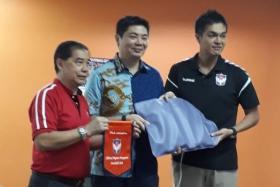 Albirex Niigata chairman Daisuke Korenaga (far right) presenting a portable Soken magnetic therapy device to Yuhua CCMC chairman Arthur Chong (centre), as Yuhua CSC chairman Lim Chock Sing looks on.