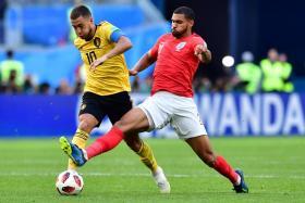 Belgium's Eden Hazard shaking off the challenge of England's Ruben Loftus-Cheek.