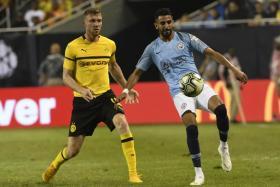 Riyad Mahrez making his Manchester City debut as Borussia Dortmund's Soren Dieckmann closes in.