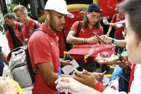 Pierre-Emerick Aubameyang (front) and Hector Bellerin (background) obliging autograph hunters after arriving at the Shangri-La Hotel on Monday morning.