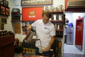 Former Spain midfielder Gaizka Mendieta trying his hand at making a cup of traditional Singapore coffee.