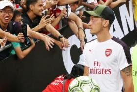 Arsenal's Mesut Oezil received a warm reception at the National Stadium in Singapore although he did not play in the match against Atletico Madrid in the International Champions Cup on Thursday.