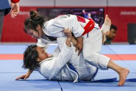 Singapore's Constance Lien (on top) defeating Thailand's Onanong Sangsirichok in the Round of 16 of the women's jujitsu 62kg category.