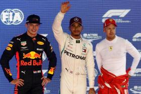 Lewis Hamilton (centre) will start on pole for the Singapore Grand Prix on Sunday, with Red Bull's Max Verstappen (left) in second spot and Ferrari's Sebastian Vettel (right) third.