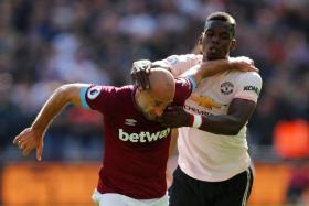 Manchester United's Paul Pogba (right) and West Ham's Mark Noble in a tussle for the ball.