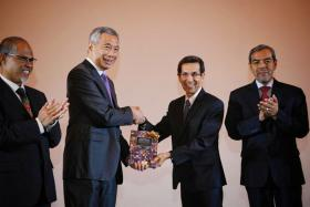 Prime Minister Lee Hsien Loong receiving a copy of the book Thriving In A Plural World: Principles And Values Of The Singapore Muslim Community from Muis president Mohammad Alami Musa at the conference to mark Muis' 50th anniversary on Wednesday. With them were Minister-in-charge of Muslim Affairs Masagos Zulkifli (far left) and Muis CEO Abdul Razak Hassan Maricar.