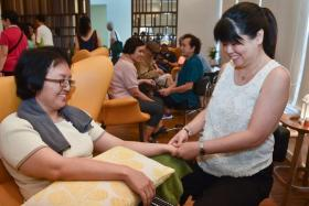 Ms Sally Low (left) receiving a hand massage from volunteer therapist Trinia Tjioe at the GoodLife!@Yishun Centre.