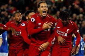 Liverpool captain Virgil van Dijk (centre) leads the celebrations after Divock Origi (far right) scored a last-gasp winner against Everton.