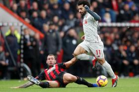 Liverpool's Mohamed Salah surging forward as Bournemouth's Steve Cook attempts to stop him.