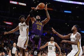 Los Angeles Lakers forward LeBron James (No. 23) moves to the basket against New Orleans Pelicans guard Jrue Holiday (No. 11) and forward Julius Randle (No. 30).