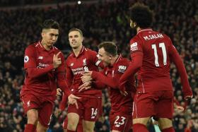 Roberto Firmino (far left) celebrates with his teammates after converting a penalty to complete his hat-trick.