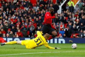 Manchester United striker Romelu Lukaku scoring their second goal past Reading goalkeeper Anssi Jaakkola.