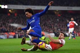 Arsenal's Sead Kolasinac tackling Chelsea forward Willian.