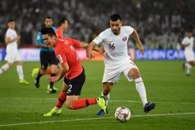 Qatar's midfielder Boualem Khoukhi (right) is tracked by South Korea's defender Yong Lee.