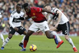 Manchester United's Paul Pogba fending off a challenge from Fulham's Calum Chambers.