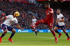 Liverpool's Georginio Wijnaldum  (in red) scoring the second goal in their 3-0 win over Bournemouth with a sublime lob.