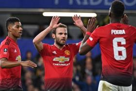 Manchester United's Juan Mata (centre) celebrating their first goal with Paul Pogba (right) and Marcus Rashford.