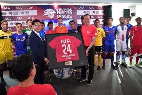 FAS president Lim Kia Tong (left) handing a framed jersey to AIA Singapore CEO Patrick Teow at a signing ceremony at Jalan Besar Stadium.