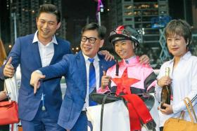 "Trainer Dennis Yip makes a ""7"" hand-sign as he celebrates with apprentice Dylan Mo and The Show's connections after saddling his 700th winner on Wednesday night."
