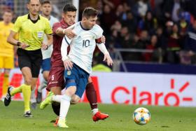 Lionel Messi trying to shrug off attention from Venezuela's Junior Moreno.