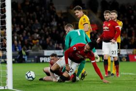 Chris Smalling scoring an own goal after being entangled with his own goalkeeper David de Gea.